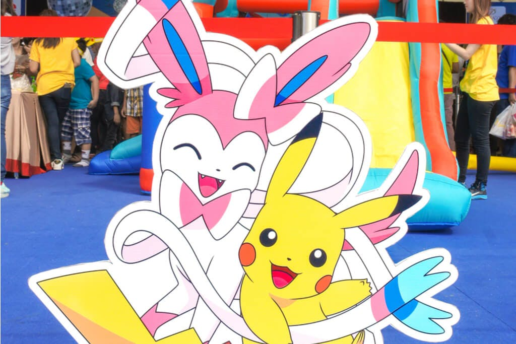 A Sylveon and a Pikachu cardboard cut-out at an event in front of many people.