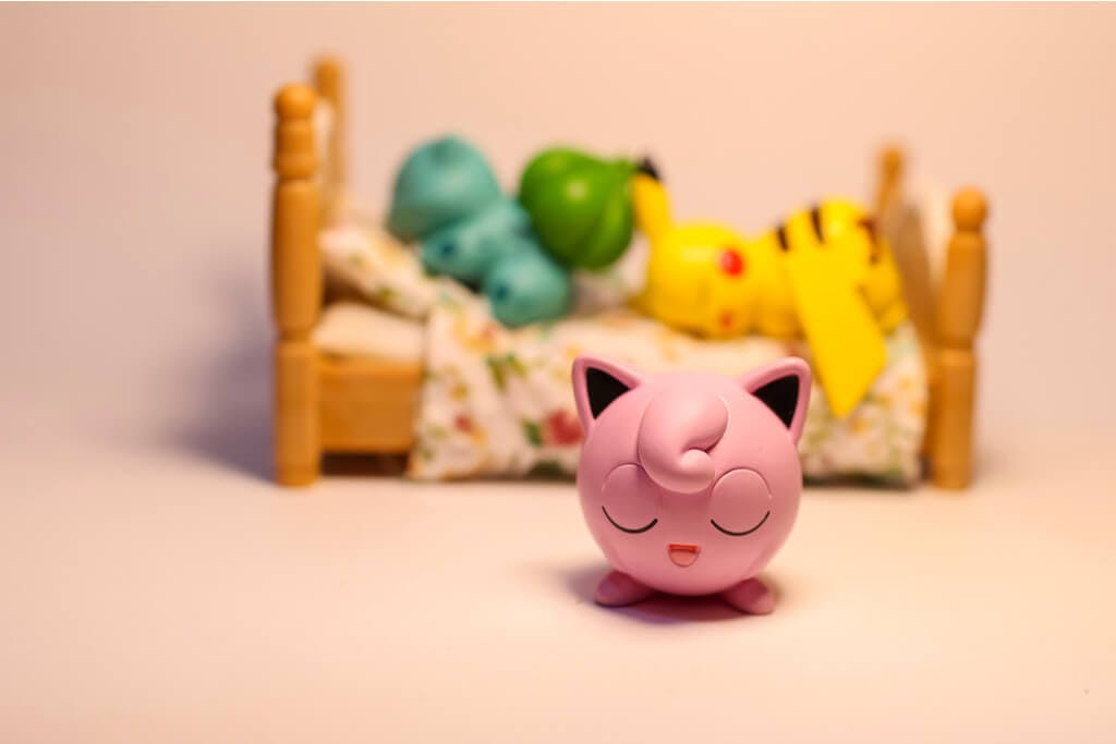 A Jigglypuff figure singing in front of a Pikachu and Bulbasaur sleeping on a bed.
