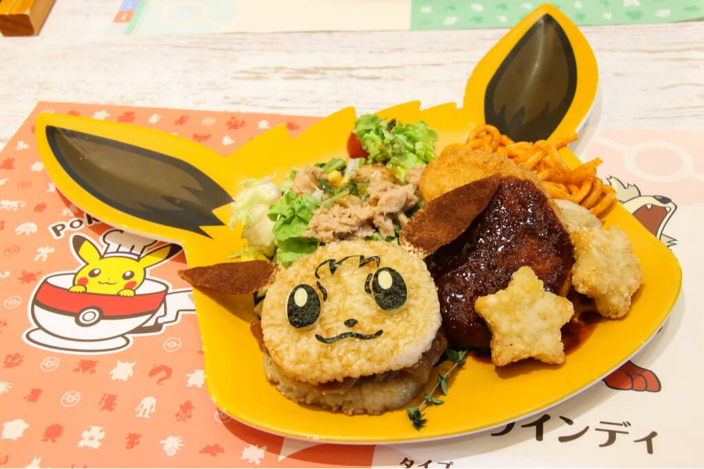 The Pokemon Cafes Eevee plate with an eevee rice burger, sides and a pokemon placemat underneath.