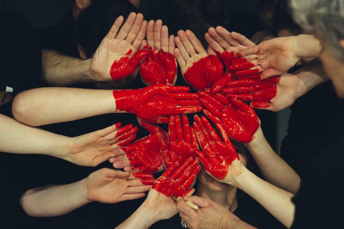 Des mains peintes formant un coeur, symbole de la communauté - Photo by Tim Marshall on Unsplash