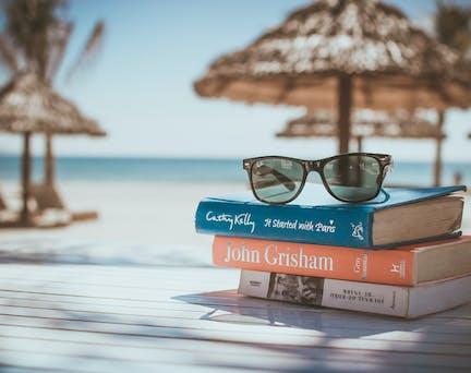 Lunette de soleil et livre posés sur une table à la plage