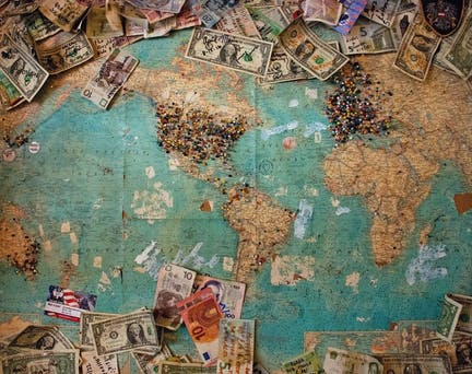 banknotes from different countries on a world map