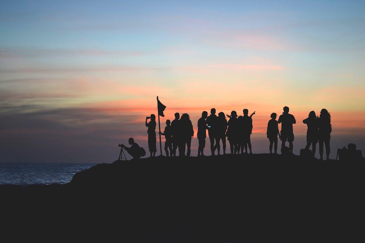 Plan d'une équipe qui a grimpé un rocher au coucher de soleil - Photo by Javier Allegue Barros on Unsplash