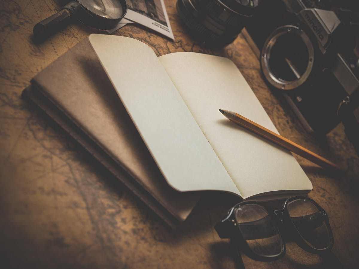 A notebook with a pencil in the middle of a card, magnifying glass, camera - Photo by Dariusz Sankowski on Unsplash