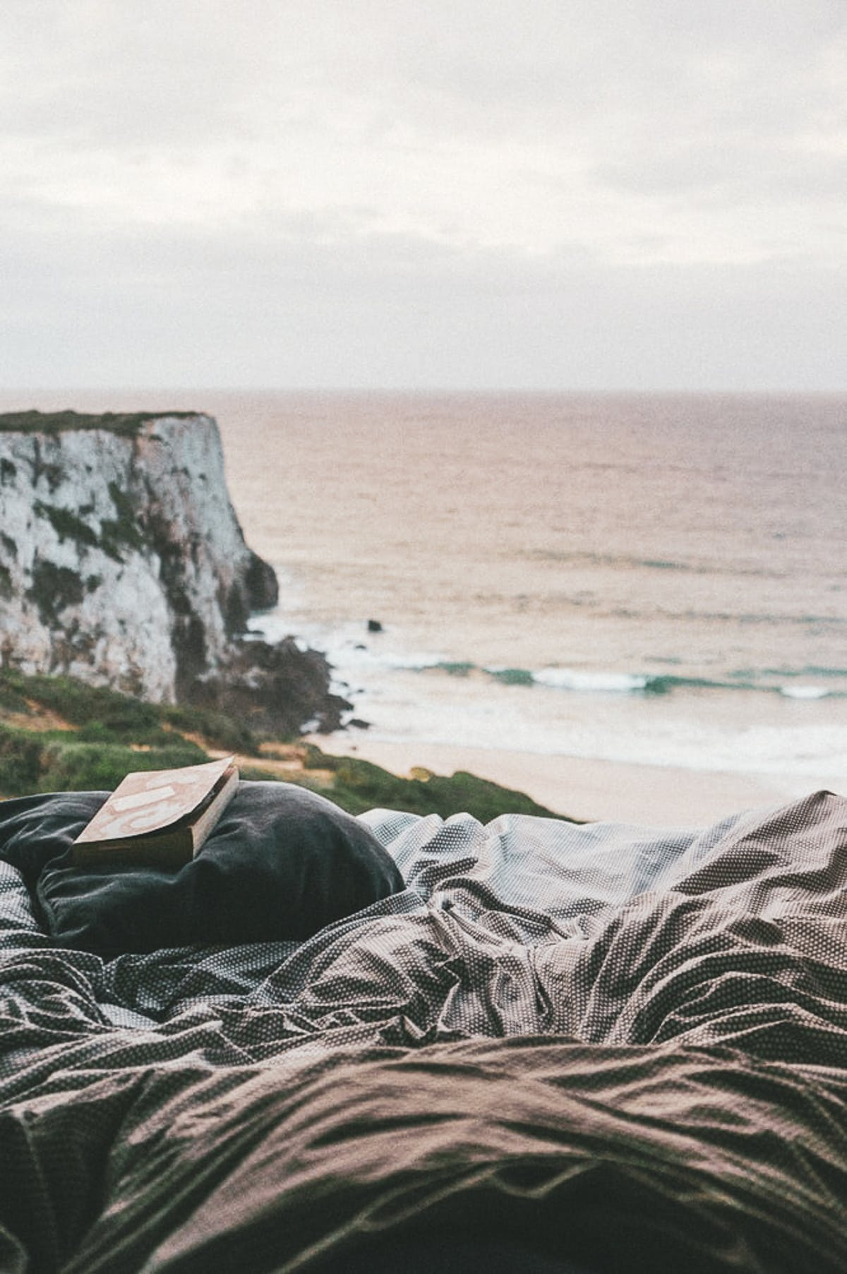 Book on a bed facing a cliff overlooking the sea