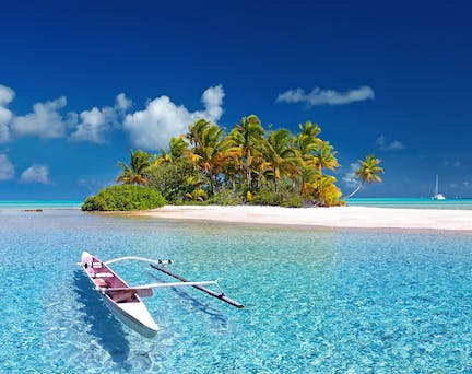 Desert island with palm tree, swinging pirogue and turquoise clear water