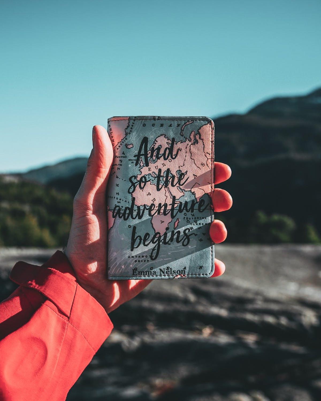 Hand holding a passport holder facing mountains