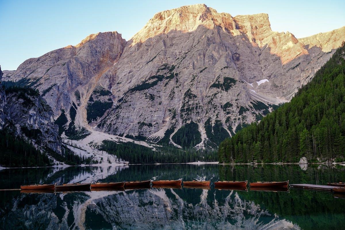 Bateaux alignés flottant sur un lac d'Italie avec des montagnes en arrière plan