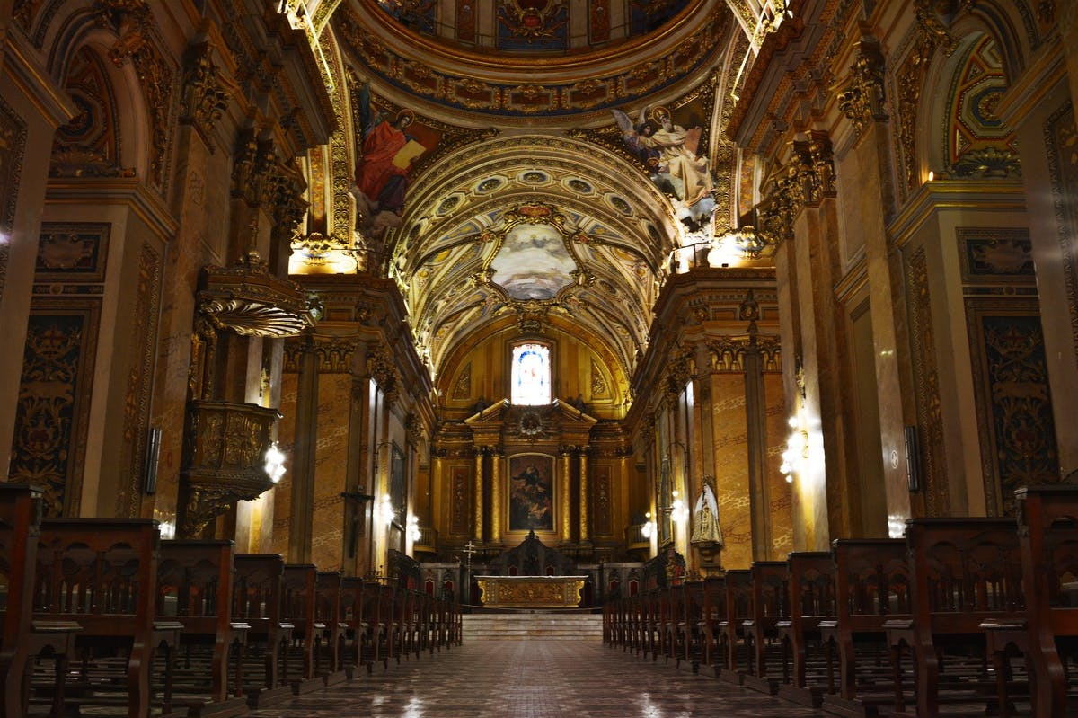 Interior of a cathedral, stone walls decorated with gold elements