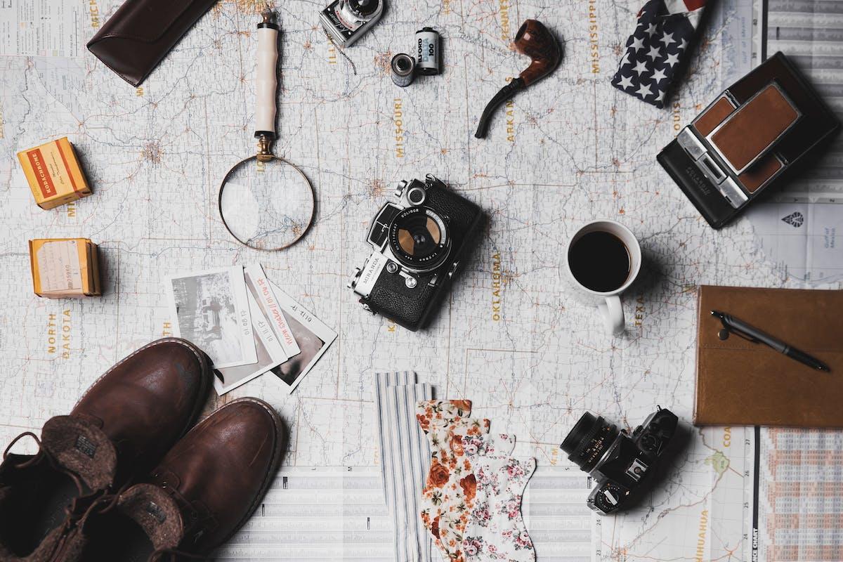 Différents objets nécessaires à un voyage sont disposés sur une carte du monde