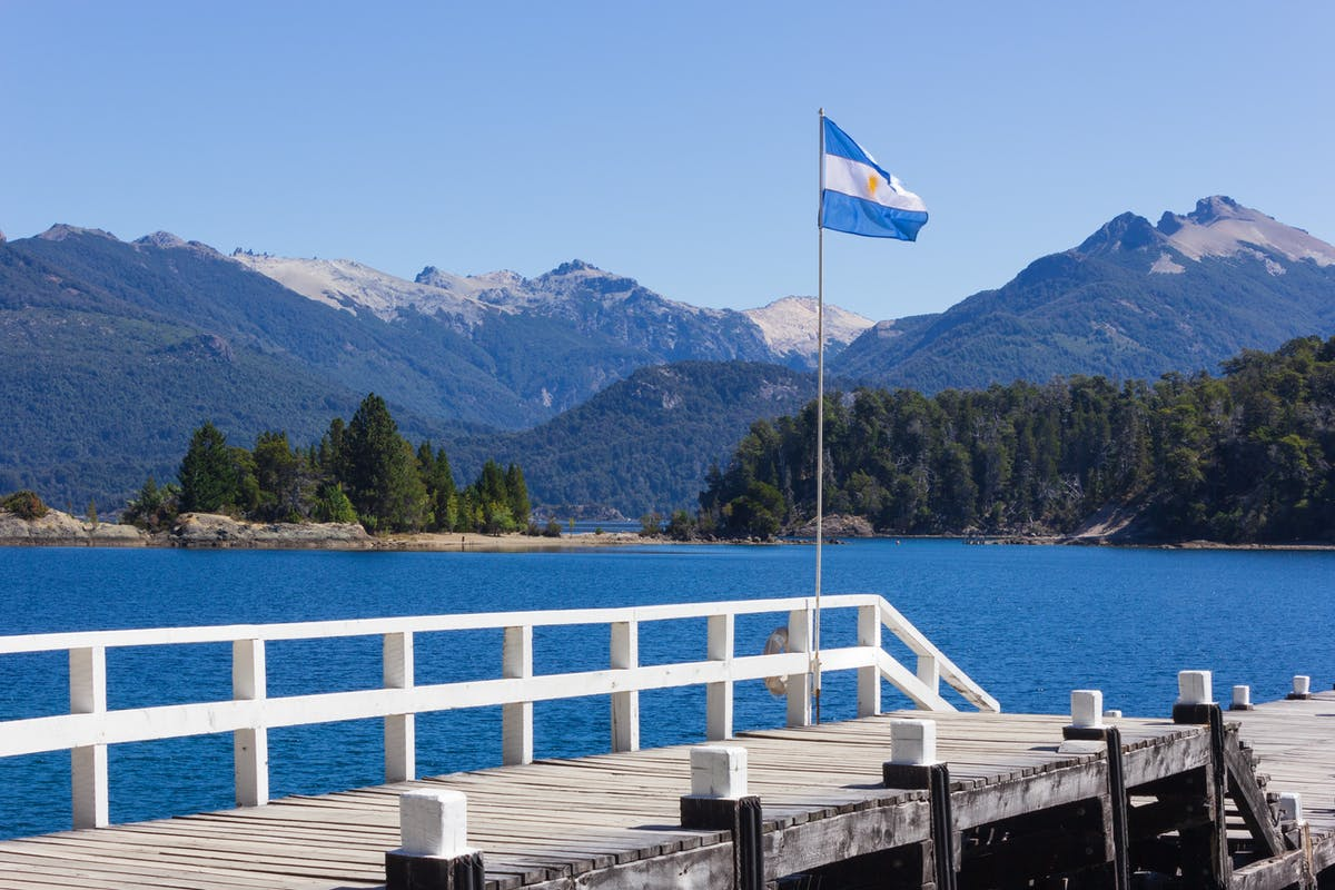 Mountains overlook a lake on which there is a wooden pontoon.