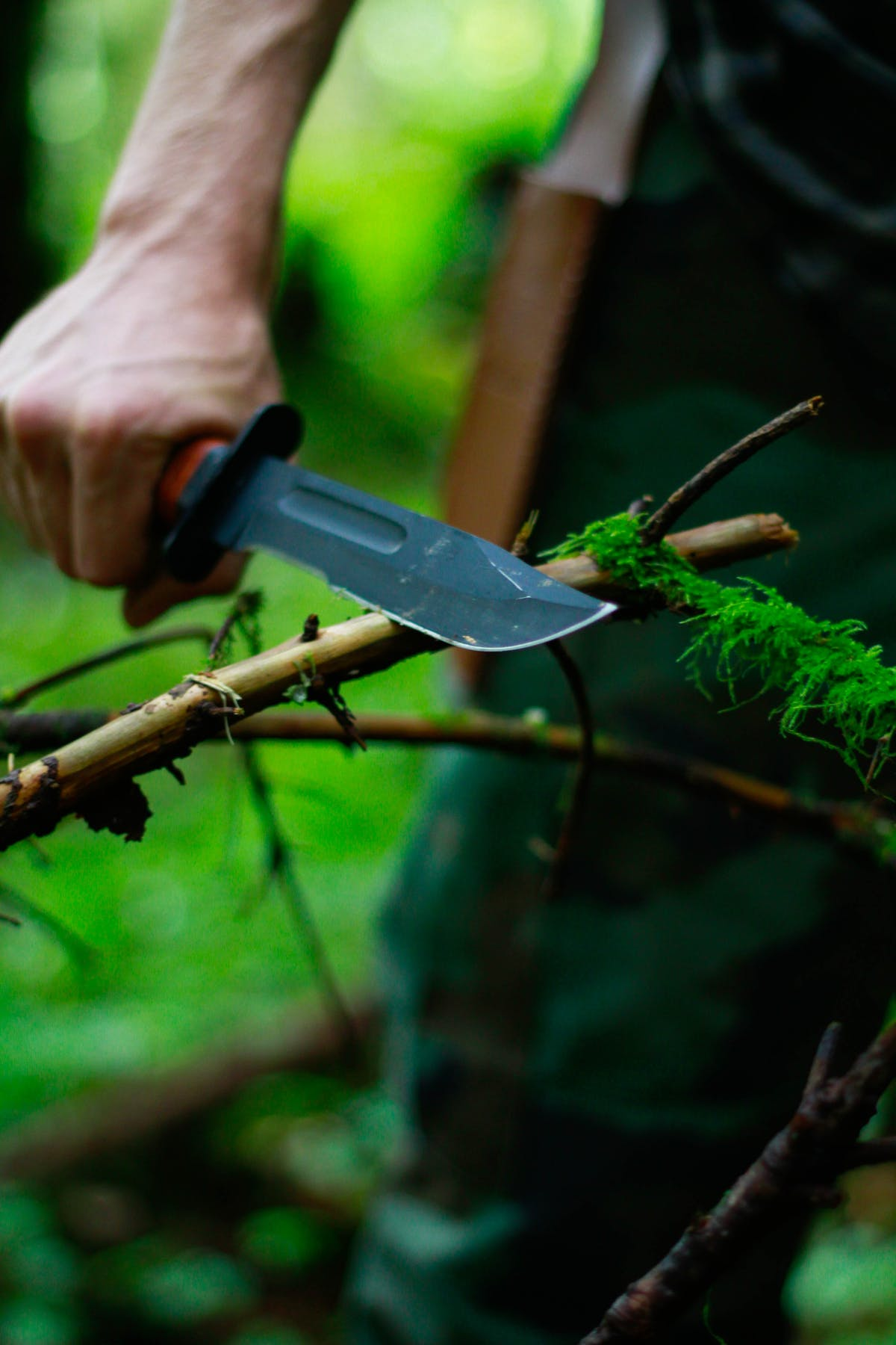 A man with a survival knife cuts a branch - Photo by 2 Bro's Media on Unsplash
