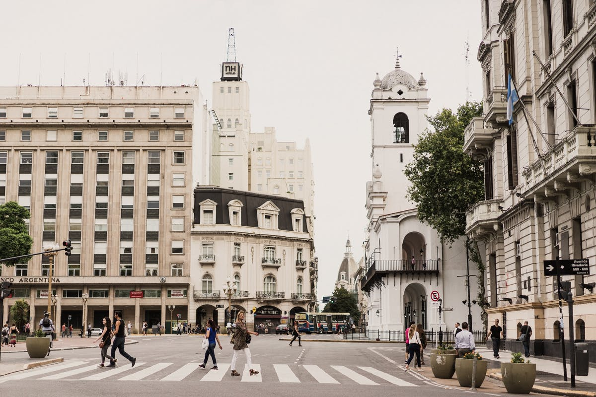 A city whose buildings are made of white stone, people crossing the pedestrian passage