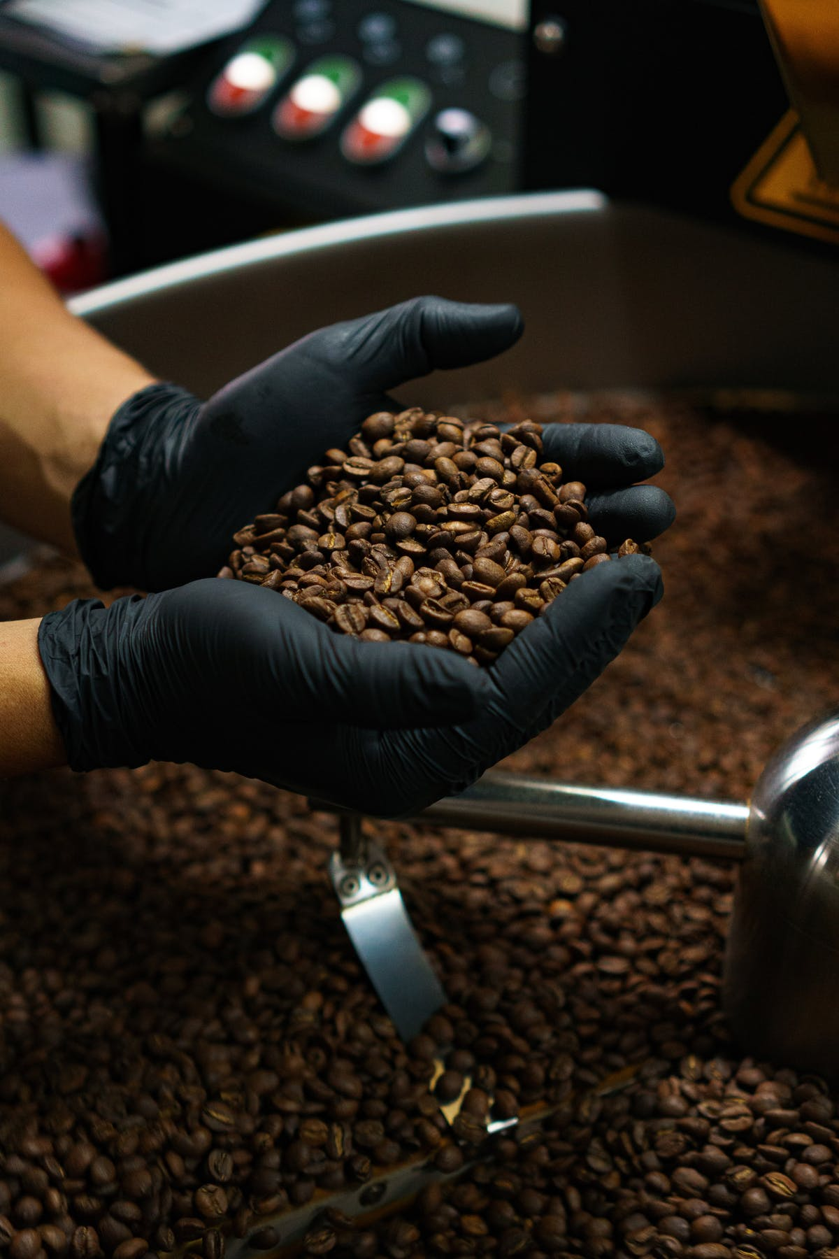 A person wearing black gloves holds coffee in his hands.