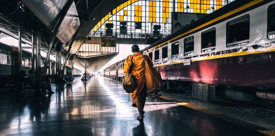Buddhist monk carrying bags and on the station platform