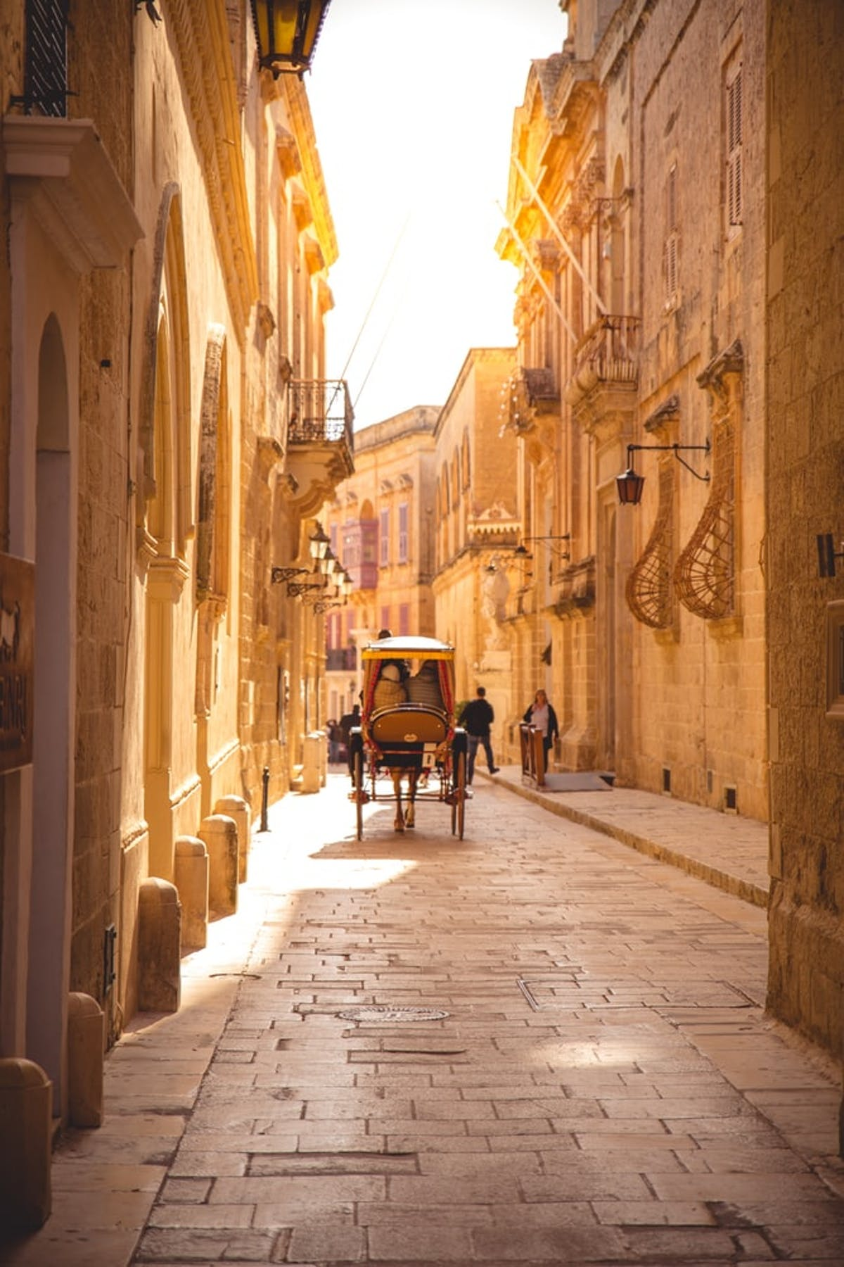 Small alley of Mdina with a horse-drawn carriage in walk