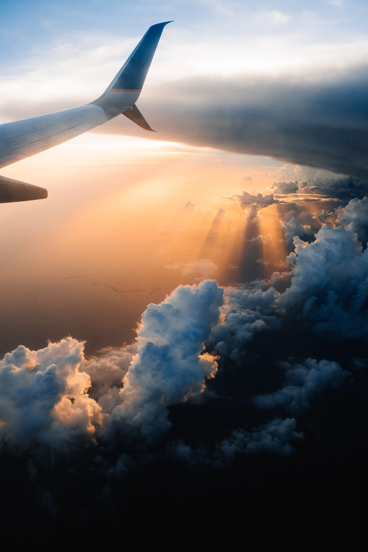Seen from a window, the setting sun behind the clouds and the right wing of a plane - Photo by Tom Barrett on Unsplash