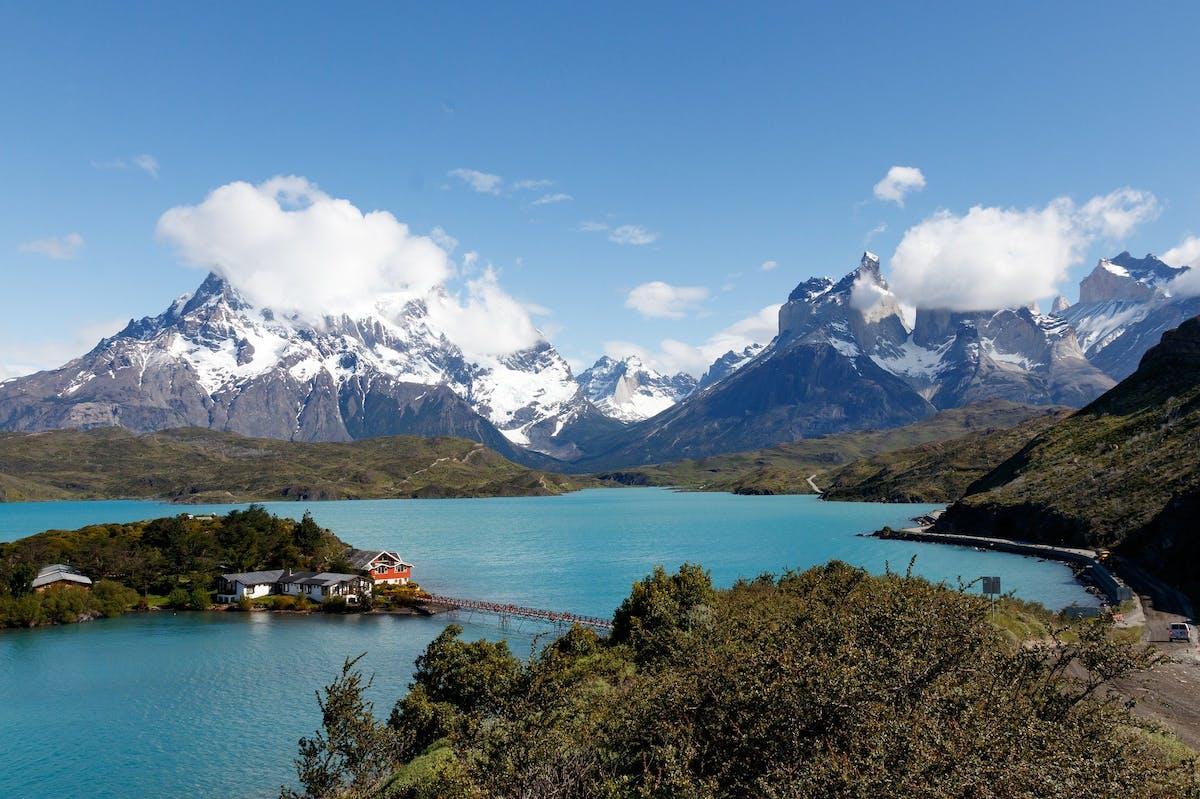 Grand lac bleu entourée de montagne enneigée et de forêt avec des maisons sur un îlot