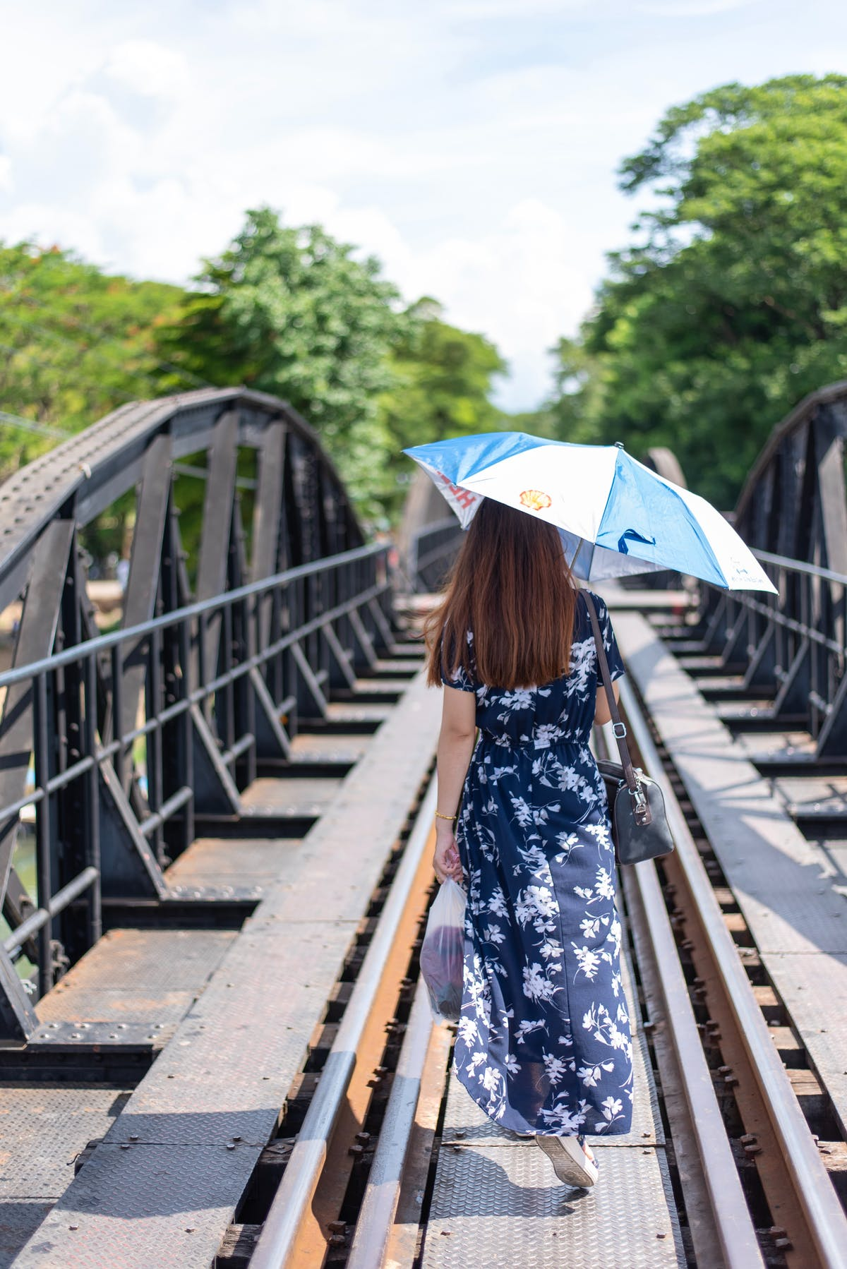 A young woman with an umbrella walks on the bridge of the river Kwai - Photo by mistermon on Unsplash