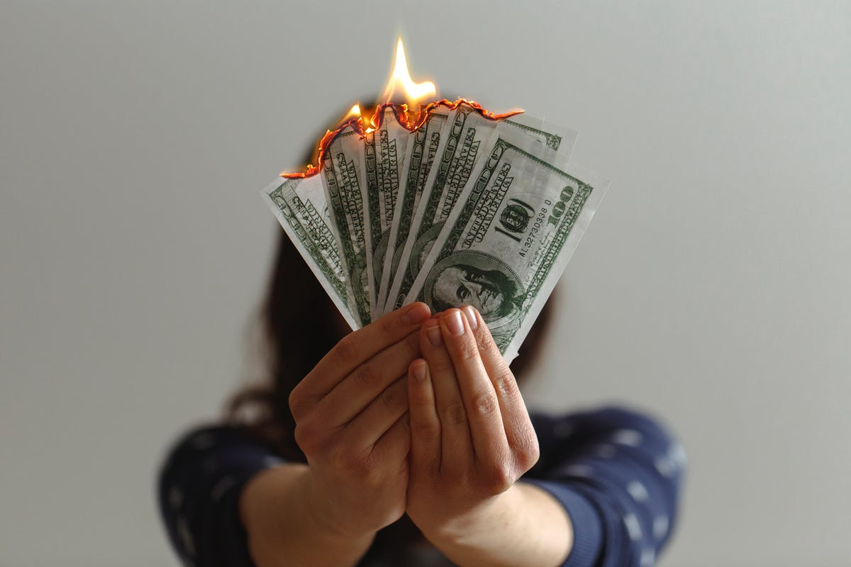 A young brown woman holds a fan of burning banknotes - Photo by Jp Valery on Unsplash