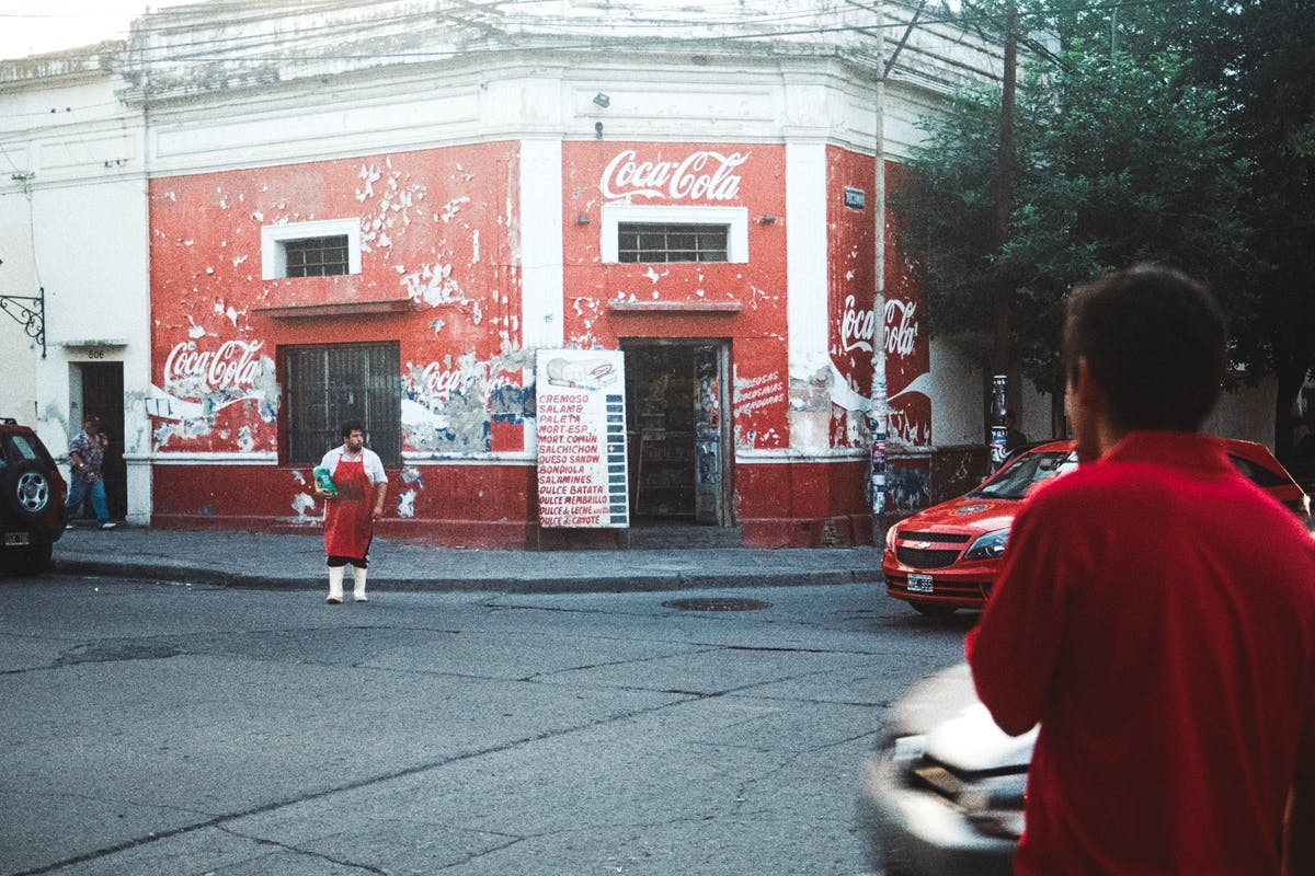 A red building with the coca cola logo erased by time, with a person in a butcher's outfit crossing the road.