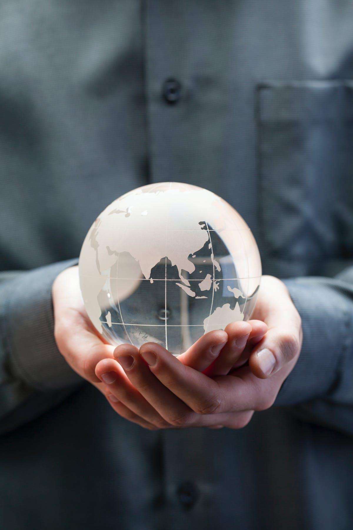 Une personne tiens une boule en forme de planète Terre dans ses mains