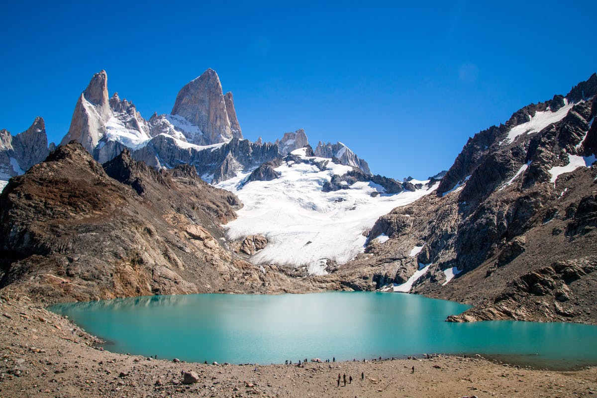 a mountain with a lake below, whose water is turquoise blue
