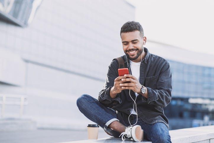 Homem sentado mexendo no celular