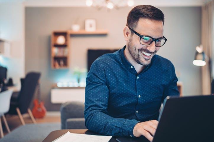 Homem sorrindo mexendo no notebook com Claro Internet