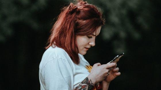 Mulher segurando celular na mão.