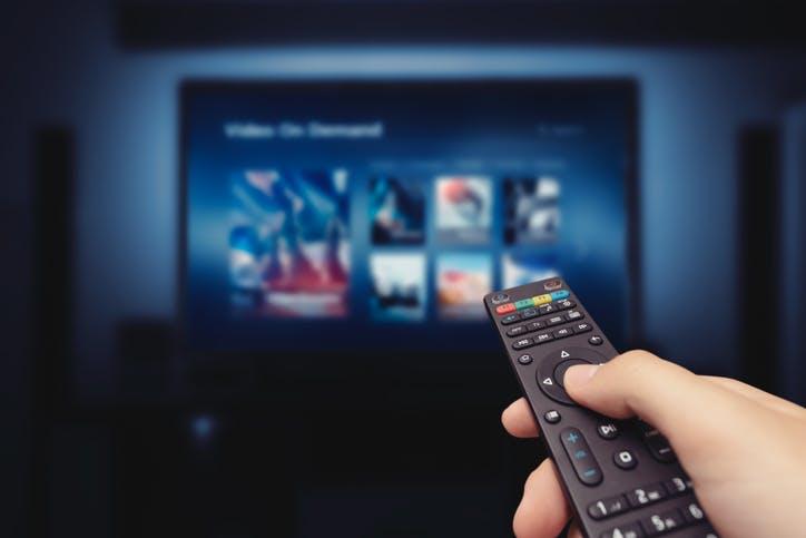 Pessoa com controle na mão mudando programação do streaming NOW