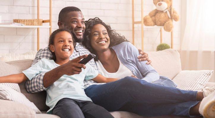 Família feliz assiste SKY TV.