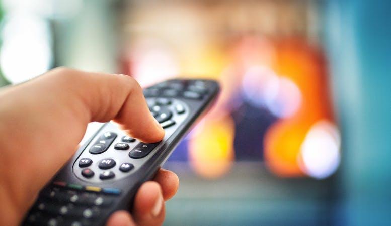 Pessoa com controle da Claro TV na mão aumentando o volume