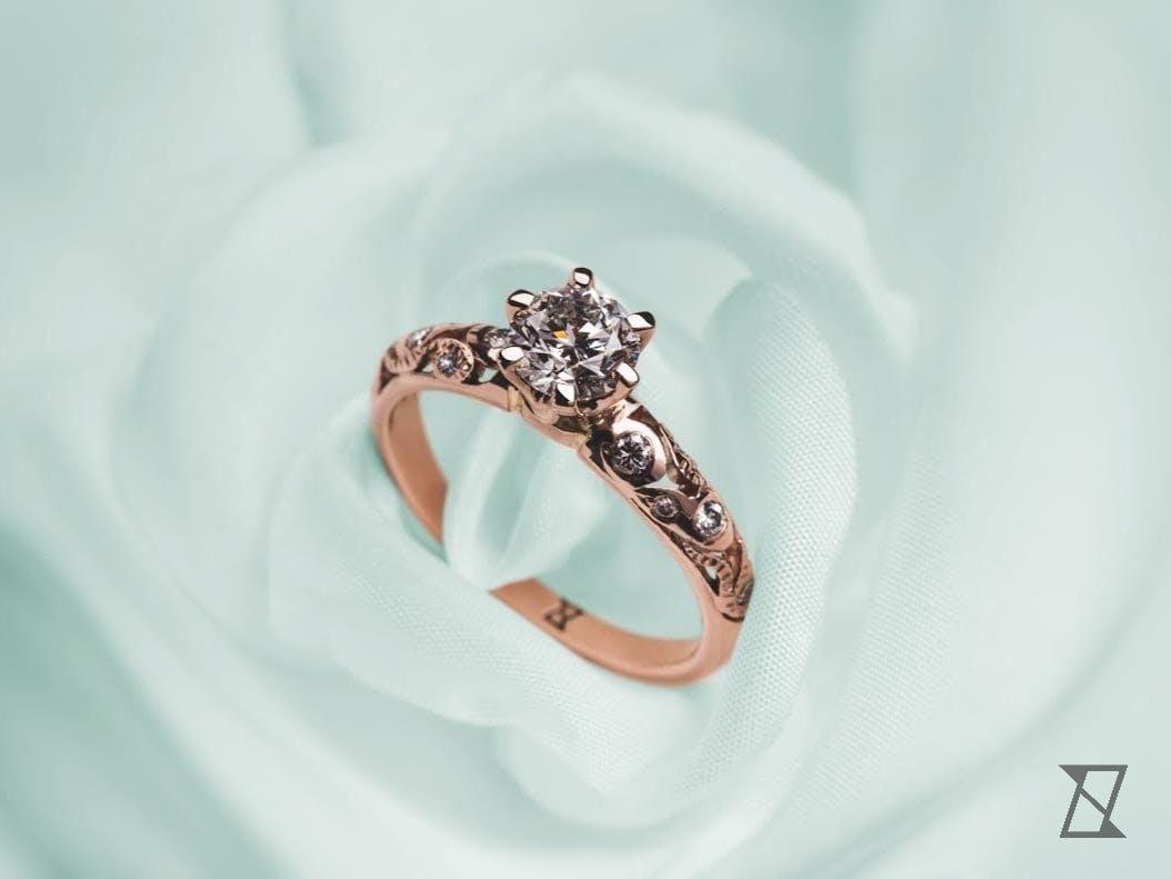 Pierścionek z diamentem w koronie wykonanej z różowego złota.