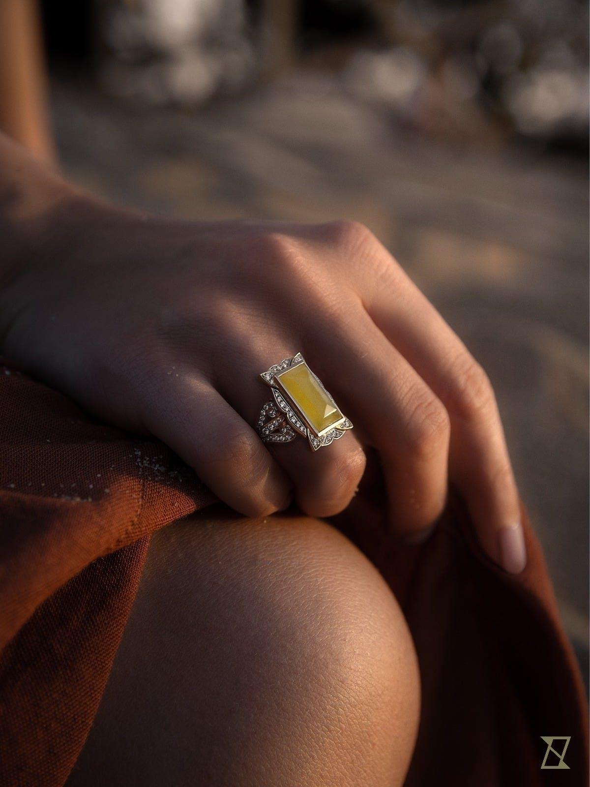 Pierścionek z bursztynem i brylantami w białym złocie skrzący się w zachodzącym słońcu na dłoni.