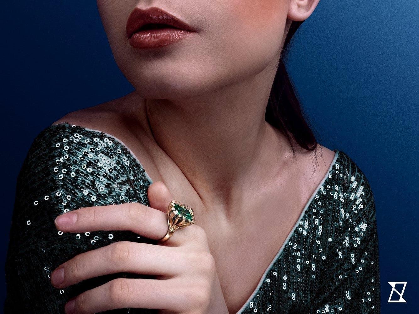 Pierścionek na dłoni modelki w zielonym złocie.