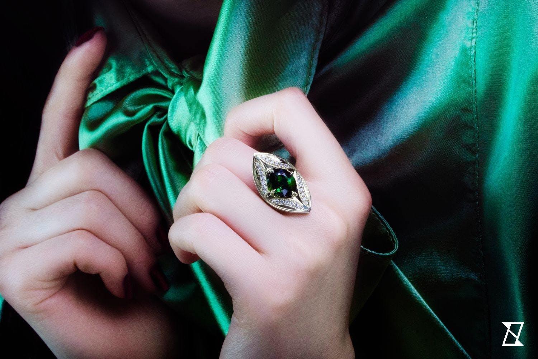 Pierścionek z zielonego złota turmalinem na dłoni.