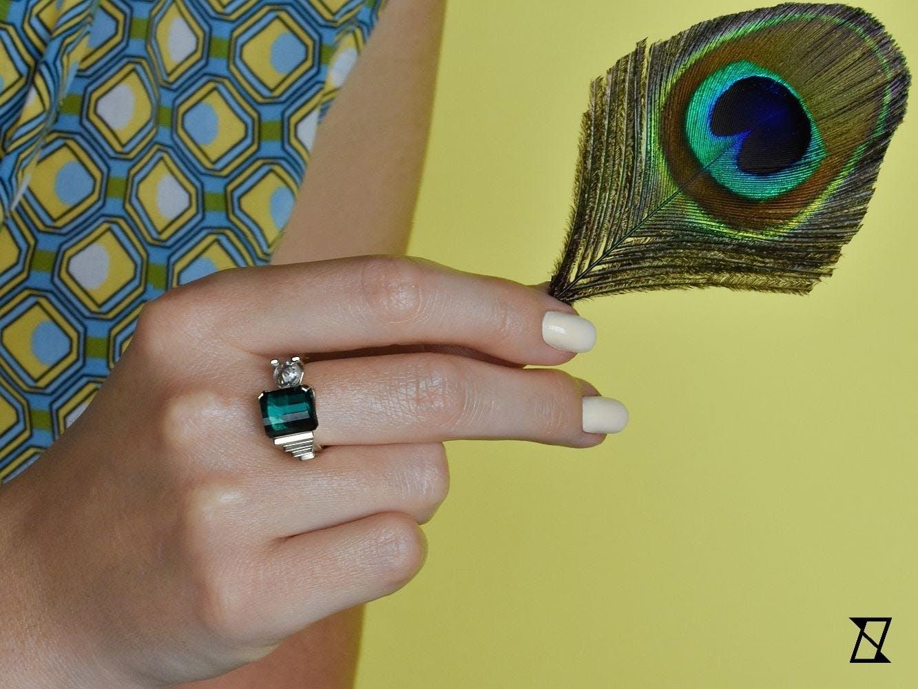 Pierścionek z turmalinem indygo na dłoni.
