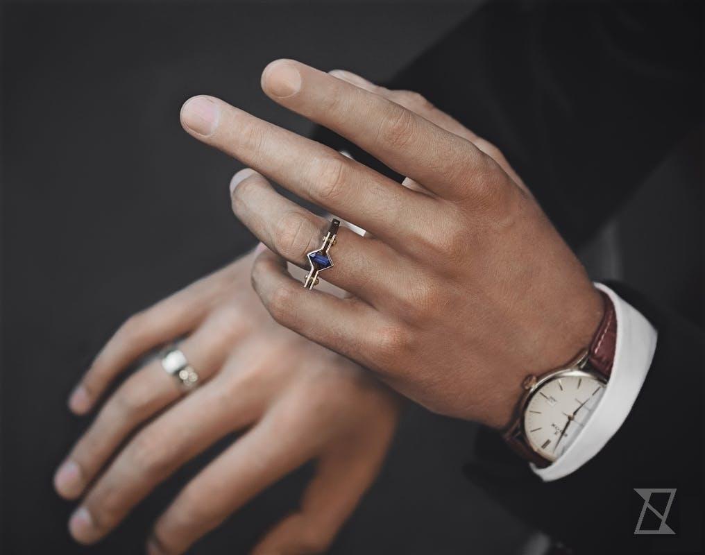 Męski pierścień z szafirem na dłoni.