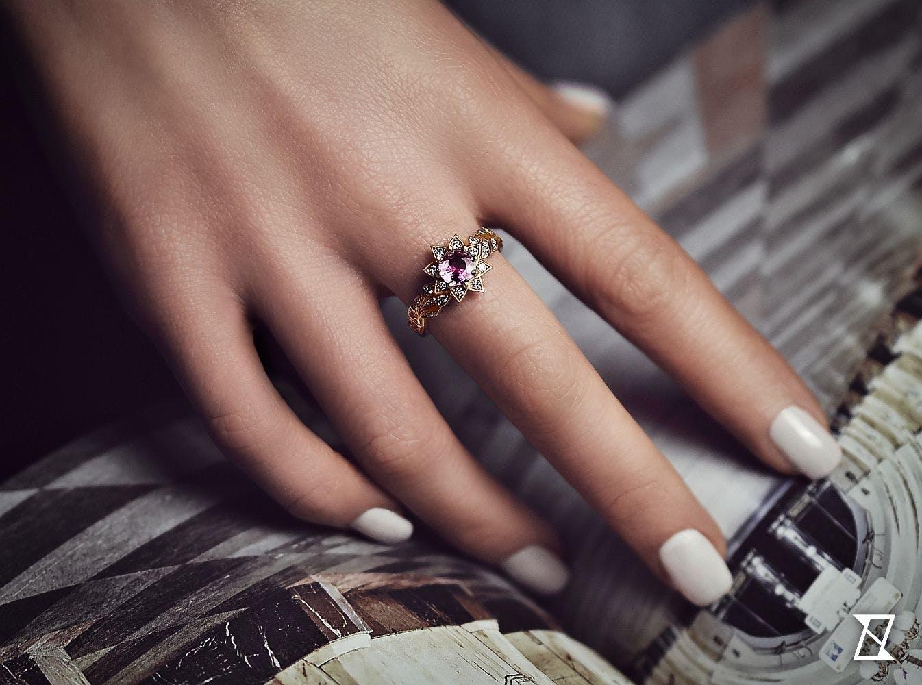 Pierścionek w kształcie kwiatu na dłoni.