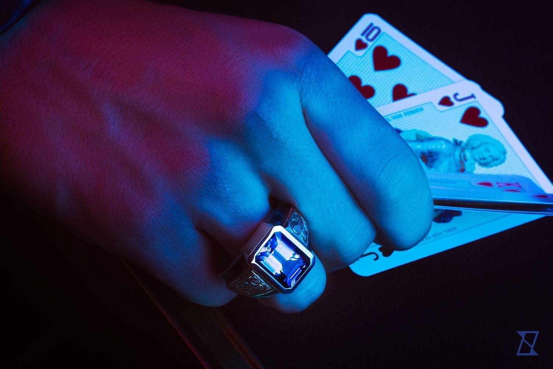 Męski pierścień z topazem na dłoni gracza wykładającego pokera.