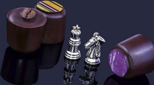 Figury szachowe z białego złota w formie naszyjników.