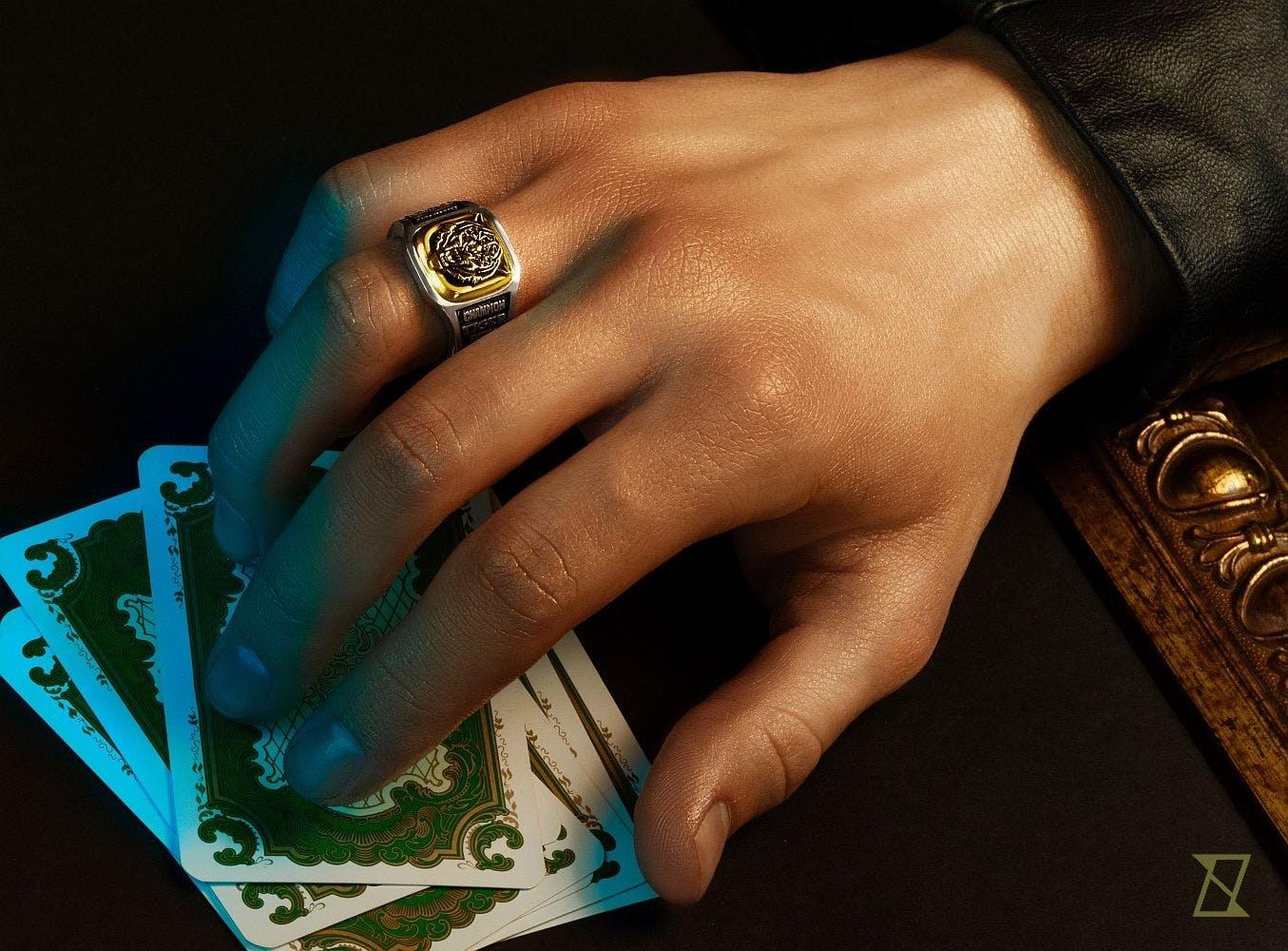 Dłoń z kartami do gry i pierścieniem z podobizną tygrysa.