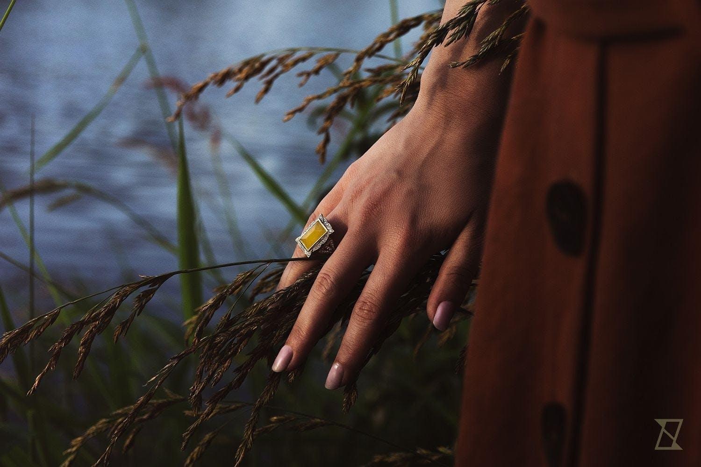 Pierścionek z bursztynem na dłoni modelki nad wodą.